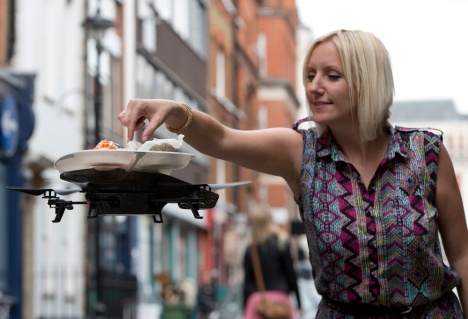 "A flying sushi service tray known as the ""itray"" is demonstrated at a ""Yo! Sushi"" restaurant in London"